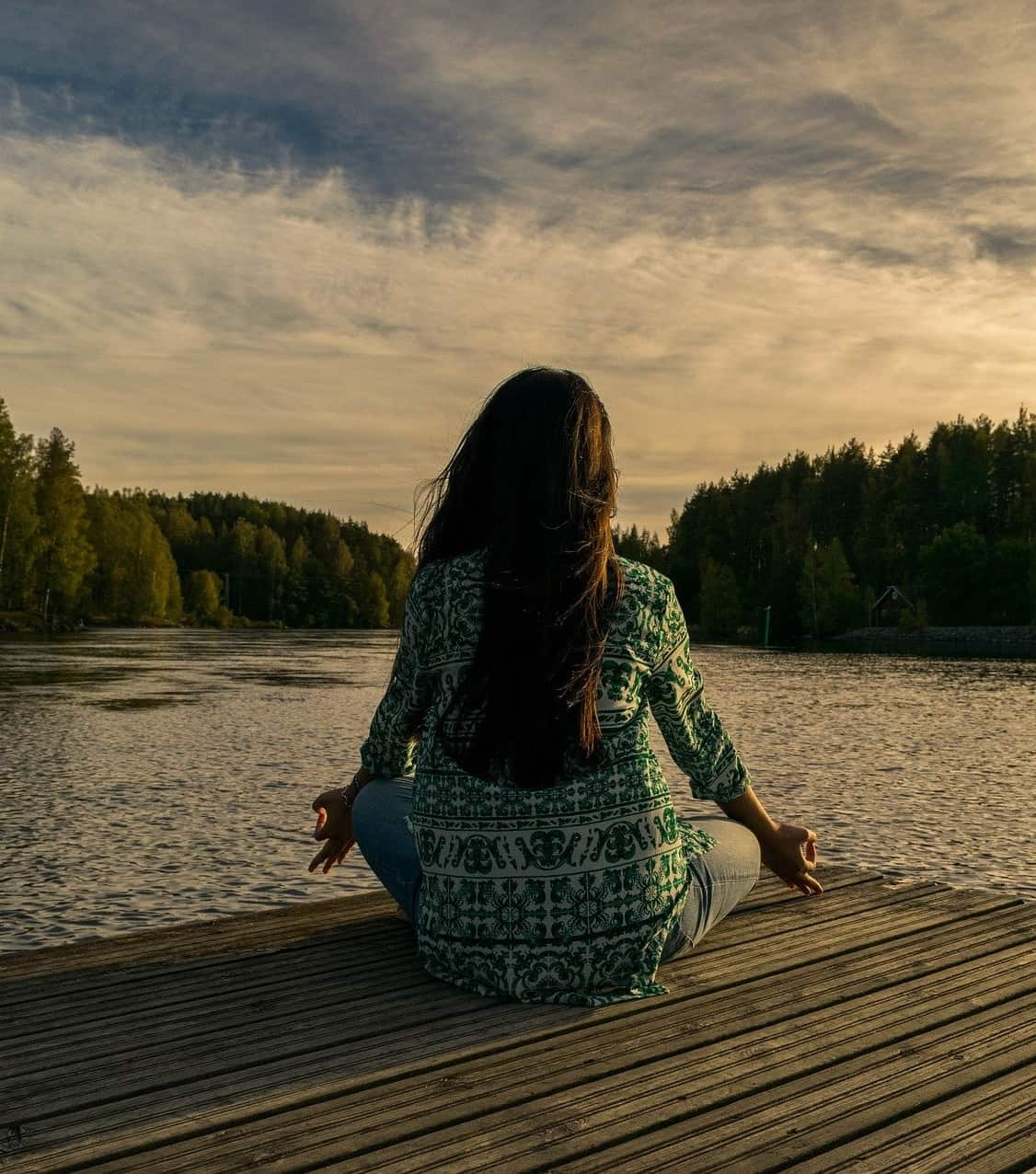 lady doing meditation by the lake