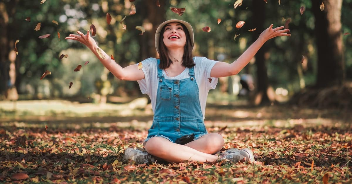 lady sitting on the fall grass happy full of energy